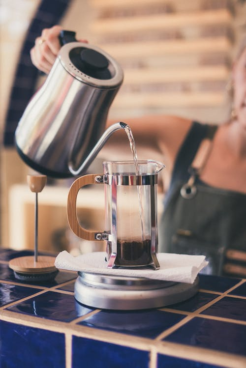 Photo of Woman Pouring Hot Water on French Press