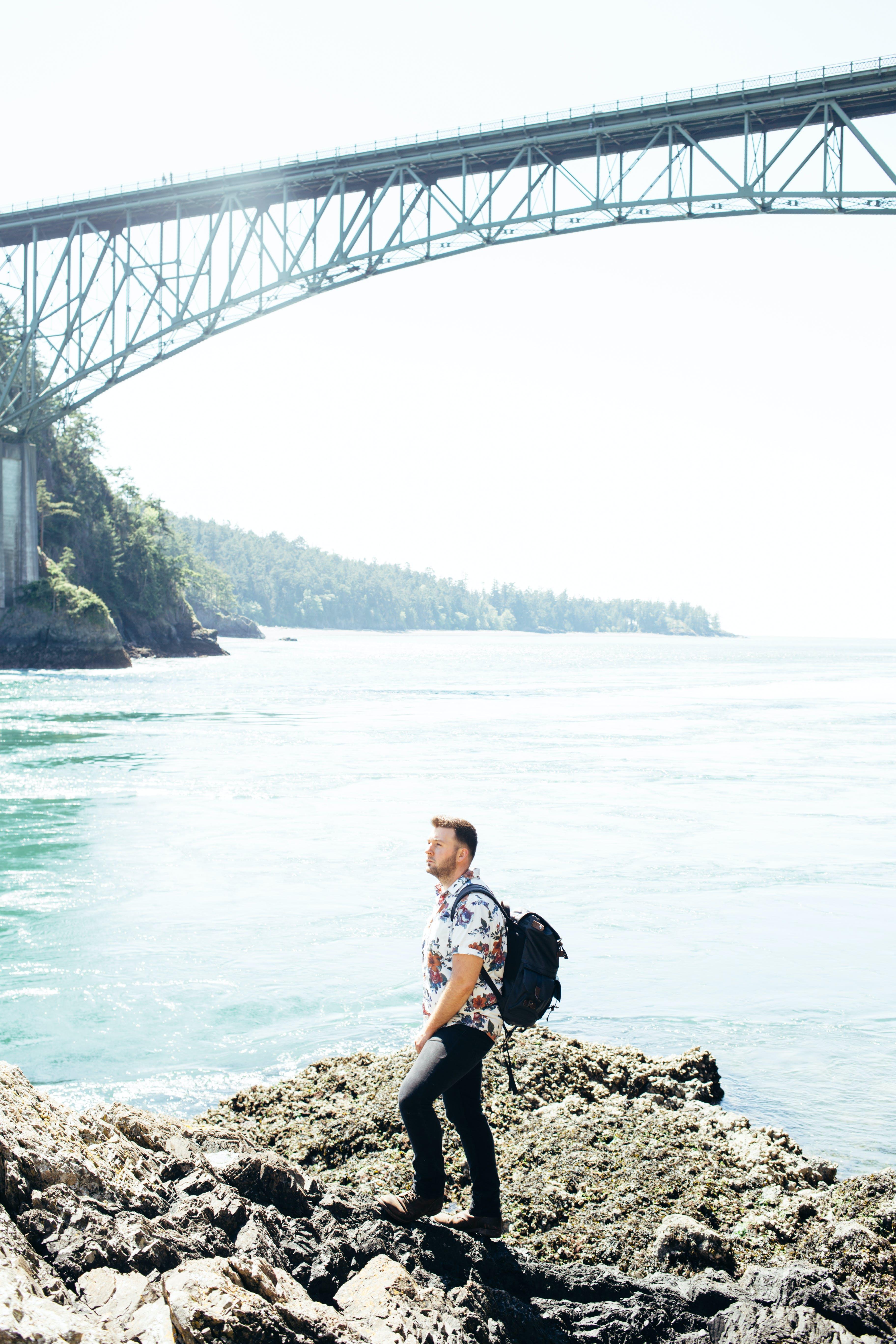 Man Standing on Gray Rock Near Gray Bridge Above Body of Water