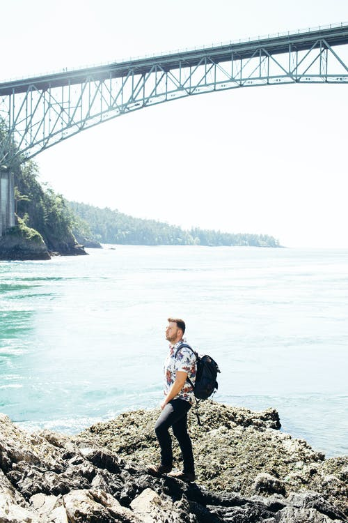 Man Standing on Gray Rock Near Gray Bridge Above Body of Water