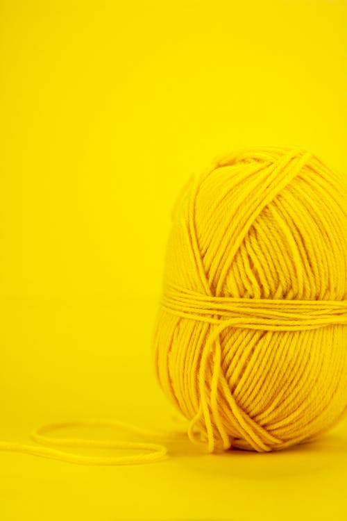 Skein of colorful yarn against yellow background