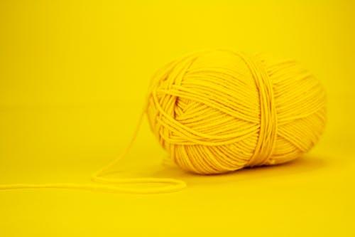 Woolen yarn lying against bright yellow background