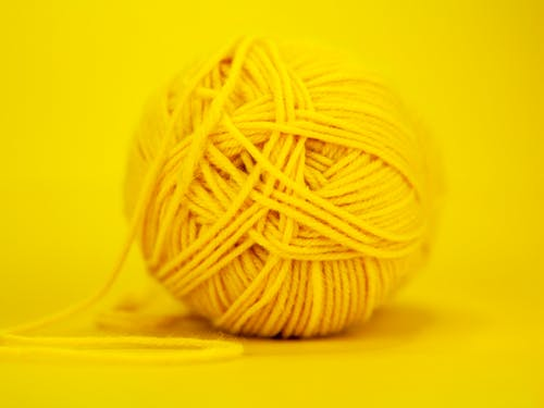 Regular ball of colorful yellow yarn placed on bright monochrome background in soft focus