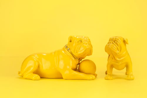 Small yellow statuettes of bulldogs with ball