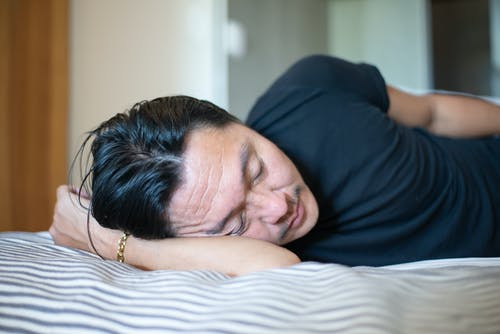 A Person Wearing Black Shirt Sleeping on Bed