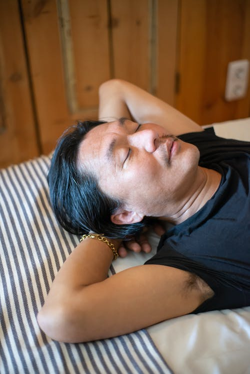 Close-Up Photo of a Man in a Black Shirt Sleeping