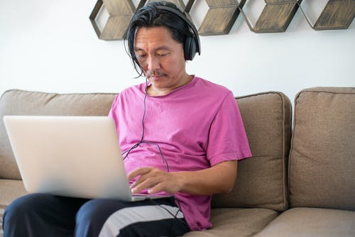 Man Sitting On A Couch Using Laptop