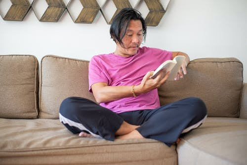 Man Sitting On A Couch Reading Book