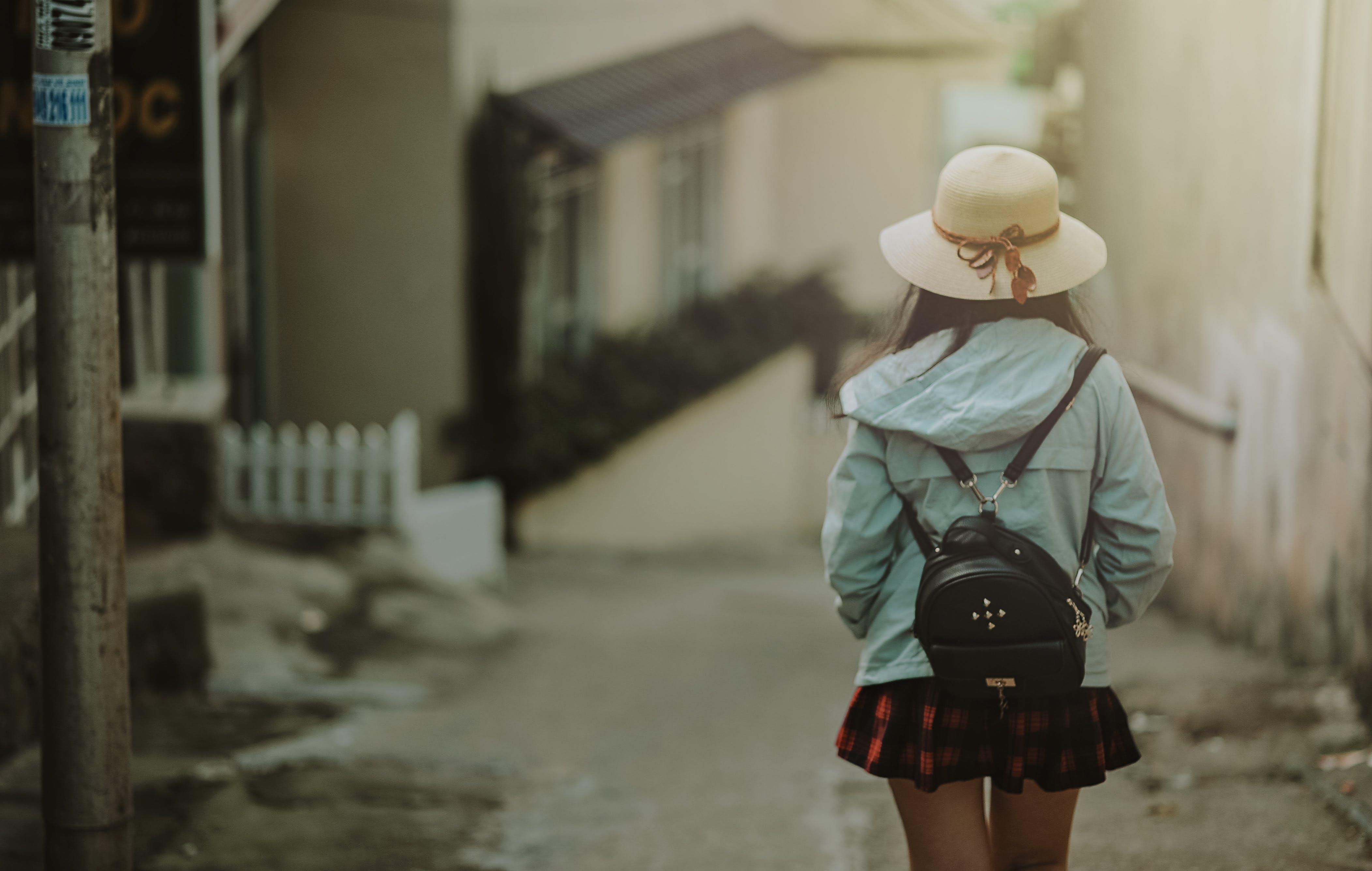 Girl in Blue Jacket and Black Leather Knapsack Walking on Street
