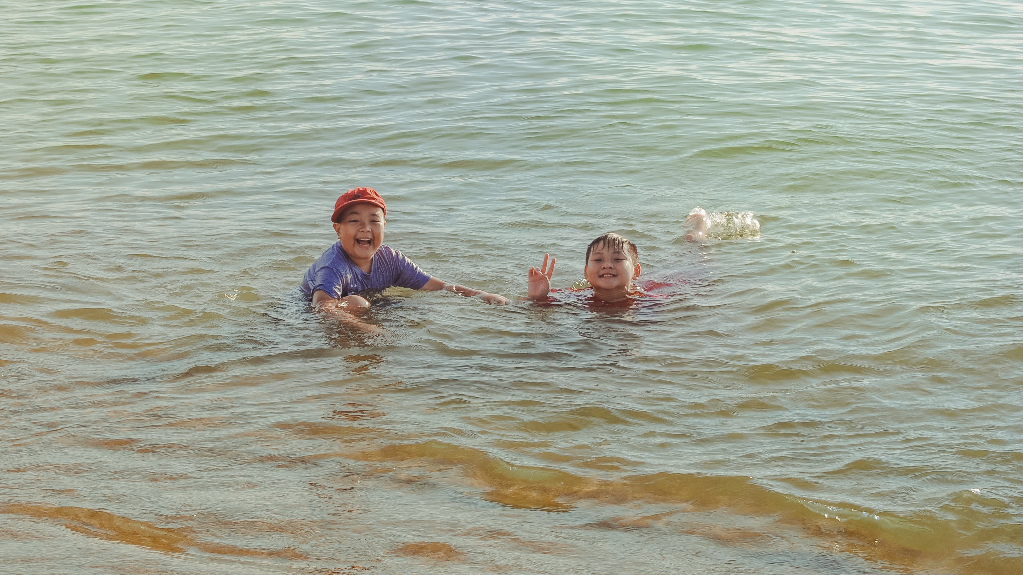 Two Boy on Brown Body of Water