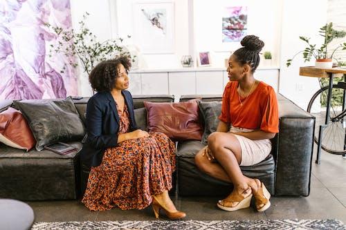 Women Sitting on a Black Leather Sofa Having a Conversation