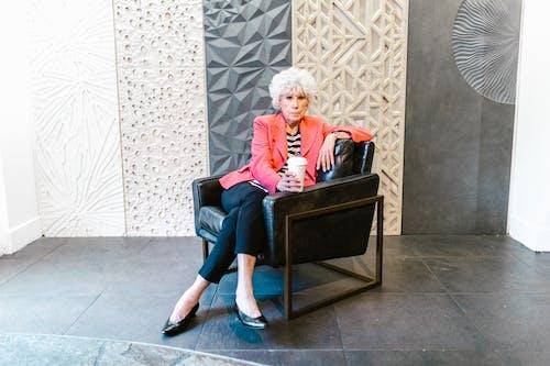 Elderly Woman in Pink Blazer Sitting on an Armchair