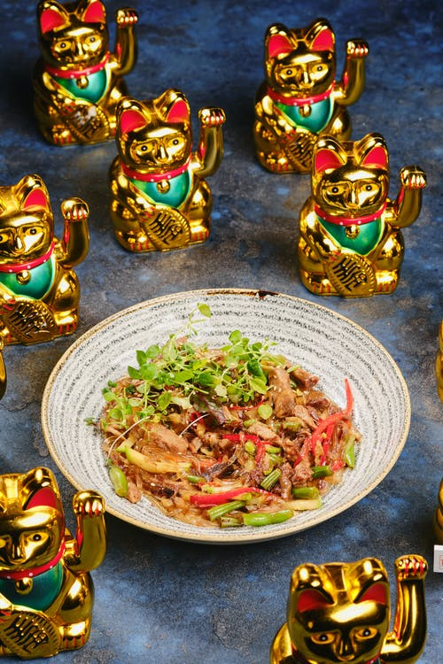 Salad on Ceramic Plate Beside Lucky Cat Traditional Ceramic Figurines