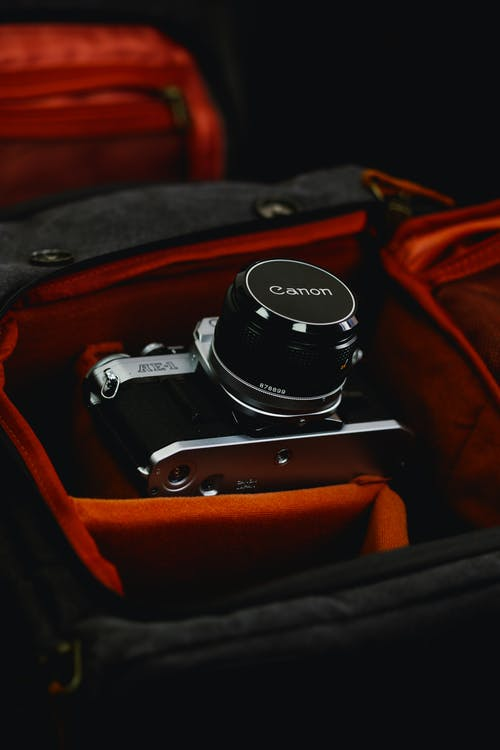 Black and Silver Dslr Camera on Brown Leather Bag