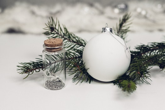 Selective Focus Photography of White Christmas Bauble Beside Bottle With Cork Lid