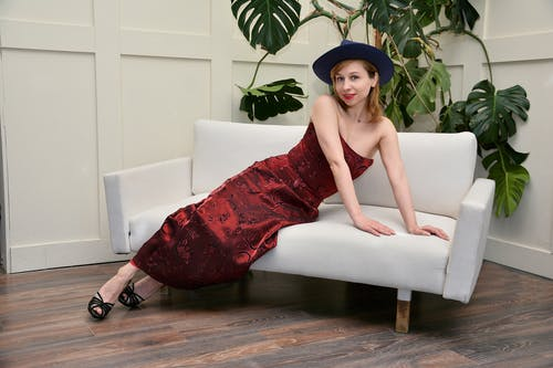 Stylish woman in hat sitting on couch