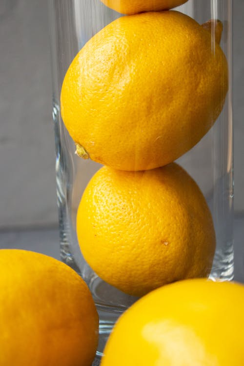 Fresh healthy lemons in glass vase placed on table