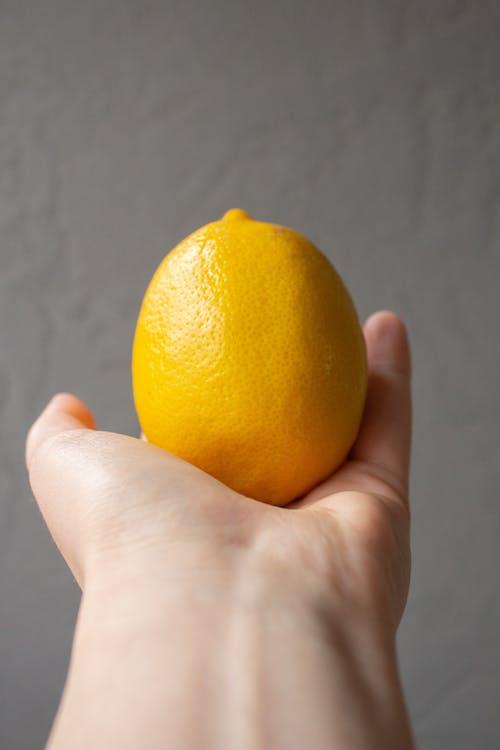 Crop unrecognizable person holding whole fresh lemon in hand