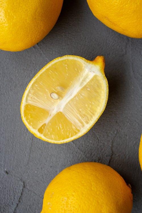 Fresh lemons scattered on gray desk