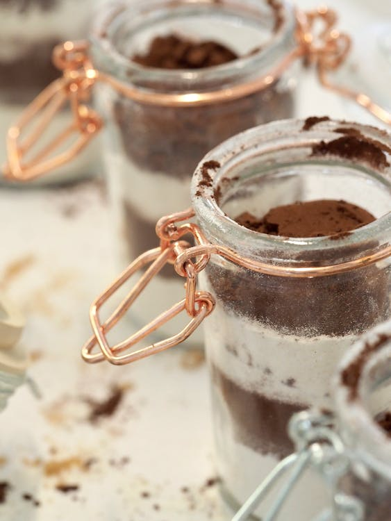 High angle of opened glass jars with sugar and cocoa powder placed on table in row