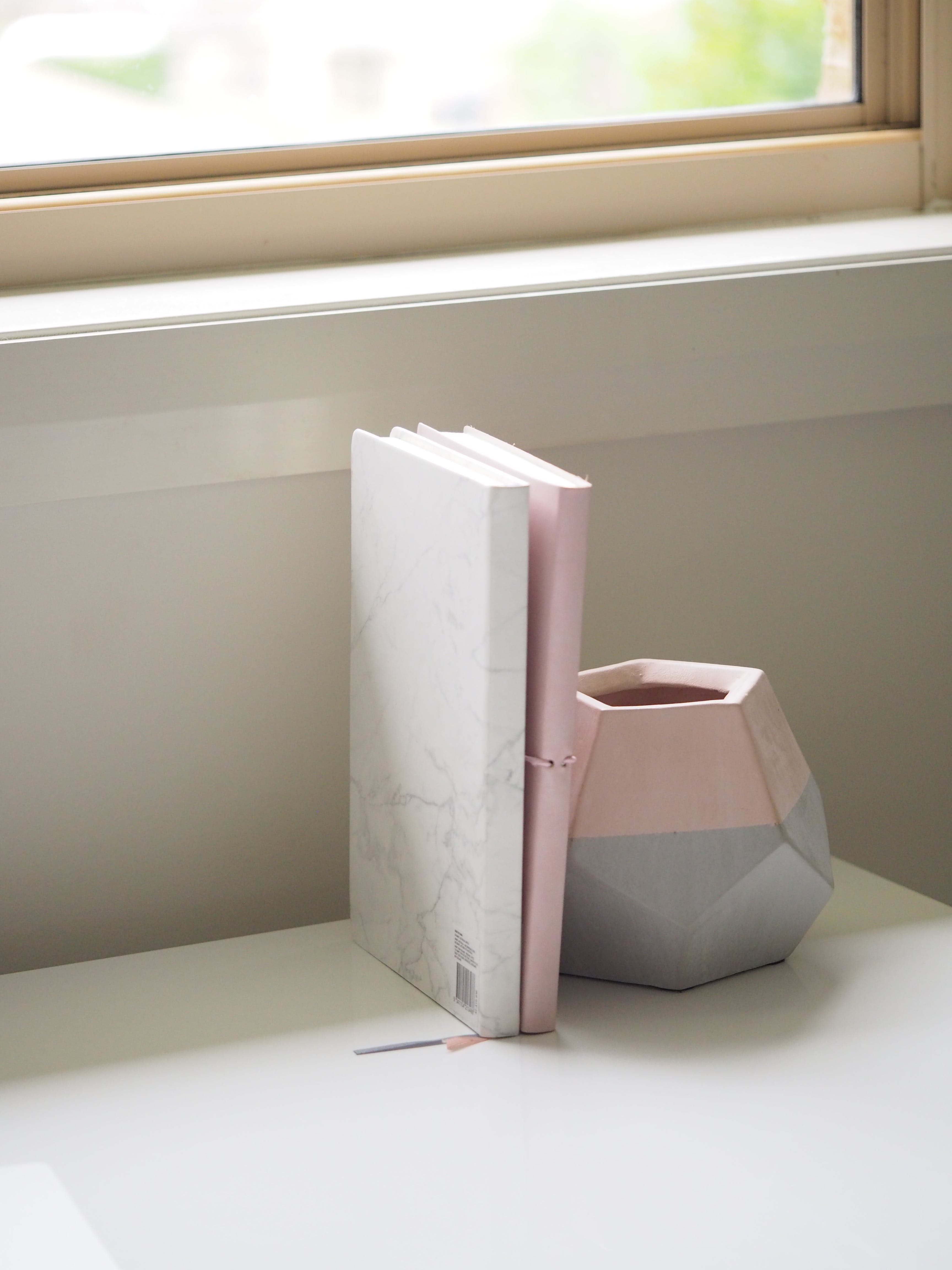 White and Pink Books Piled Beside Pink and Gray Ceramic Vase