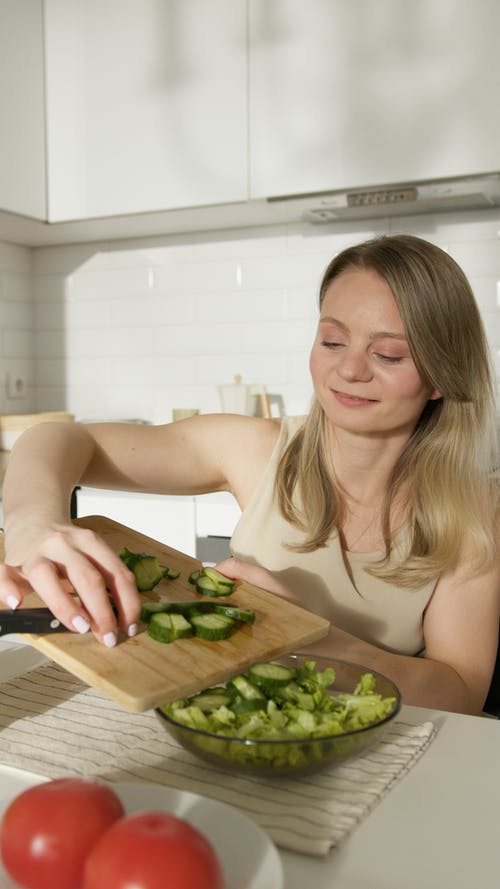 A Woman Cutting Vegetables on the Table
