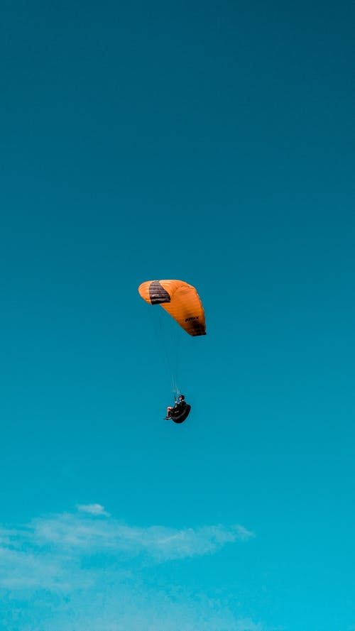 Person in Red and Yellow Parachute in Mid Air