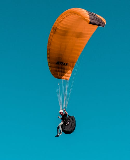 Person in Black Jacket Riding Yellow Parachute