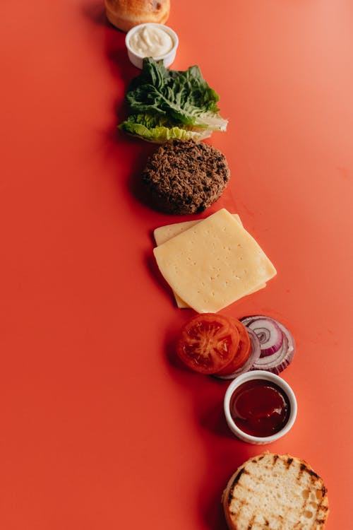 Deconstructed Burger on Red Surface