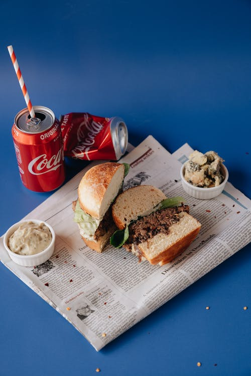 Red Coca Cola Cans Beside Burger on Newspaper
