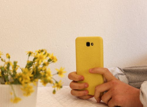 Close-Up View of a Person Holding Yellow Cellphone Case