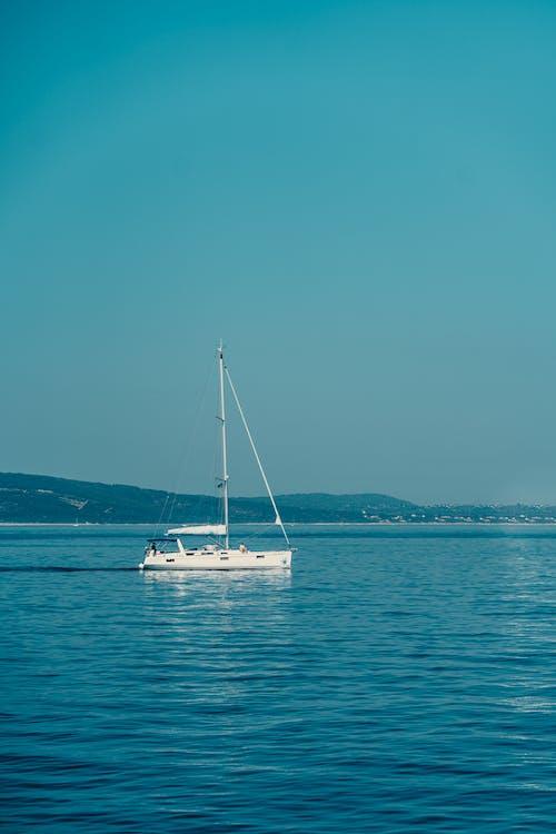 White Sailboat on Blue Open Sea Under Blue Sky