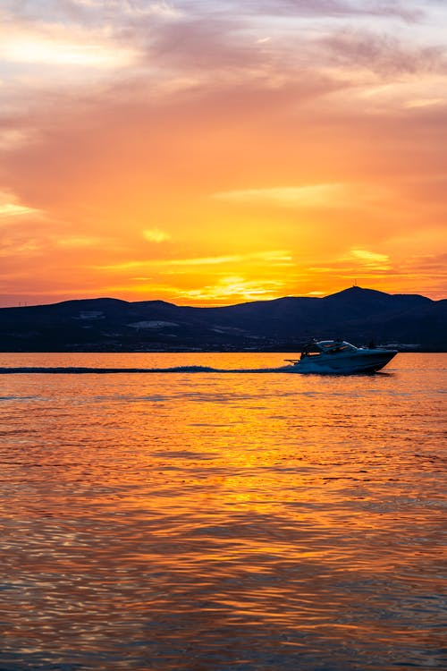 Silhouette of Speedboat on Sea during Sunset