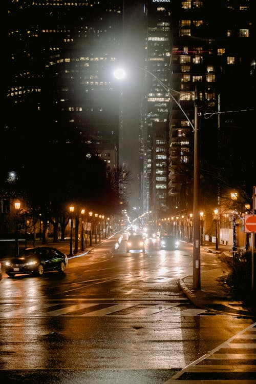 Automobiles driving on roadway between modern tall residential buildings with glowing lights located on street in dark city with streetlight
