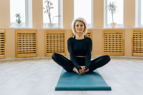 Woman Sitting on a Yoga Mat Indoors