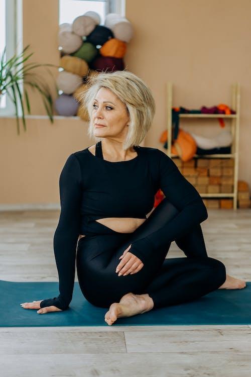 Woman Sitting on a Yoga Mat Looking Sideways
