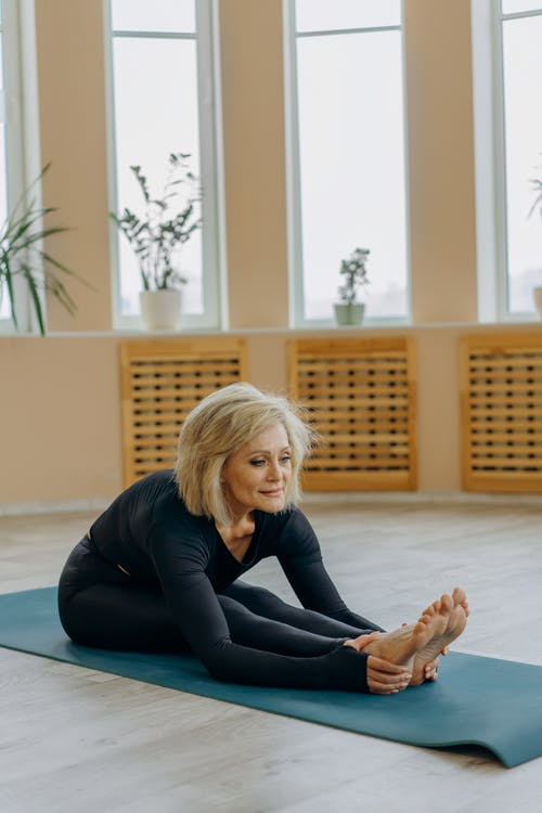 Photo of a Woman Stretching on a Yoga Mat