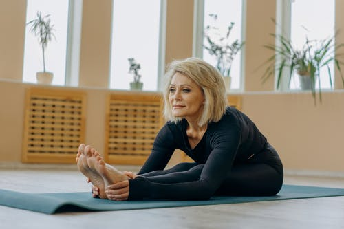 Photo of a Woman Wearing Activewear Stretching