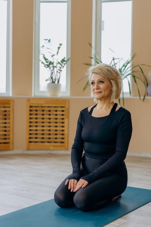 Woman Kneeling on a Yoga Mat