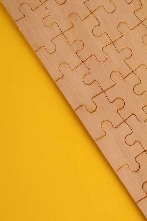 Brown Puzzle Piece on Yellow Surface