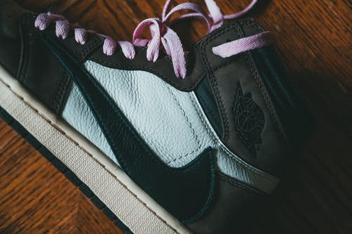 Top view of close up of modern black footwear with pink laces placed on wooden surface