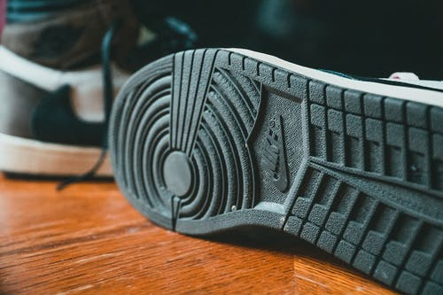 Closeup of black rubberized sole of modern stylish sneakers placed on wooden floor