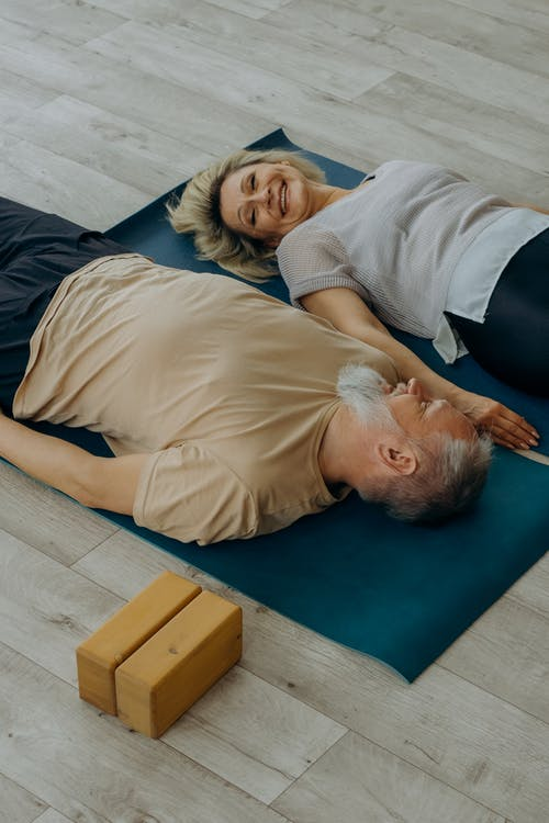 Man in White Shirt Lying on Blue Mat Beside Woman in Black Shirt