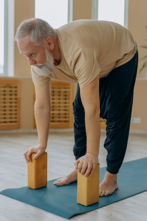 Man in Brown T-shirt and Black Pants Doing Exercise