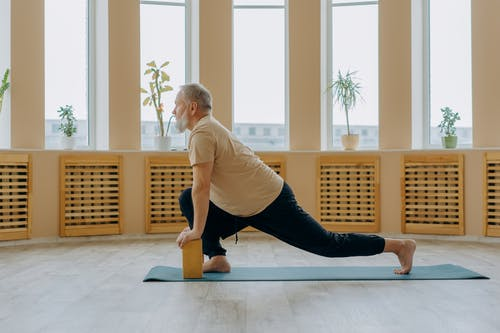 Man in White T-shirt and Black Pants Doing Yoga