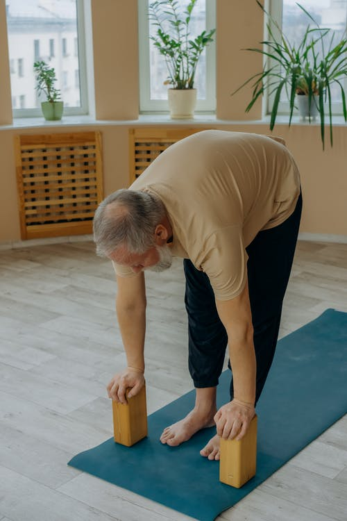 Man in Brown T-shirt and Blue Denim Jeans Doing Yoga