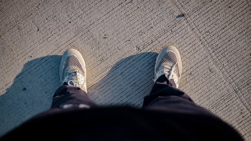 Top view of crop anonymous person in sneakers and activewear standing on road after outdoor training in sunny morning