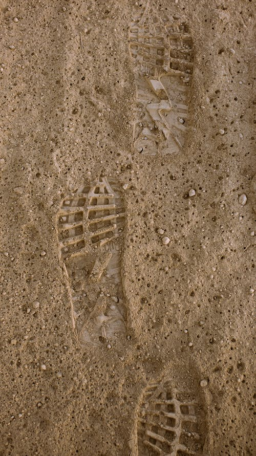 From above of textured footprints of unrecognizable person on dry sandy ground in daylight