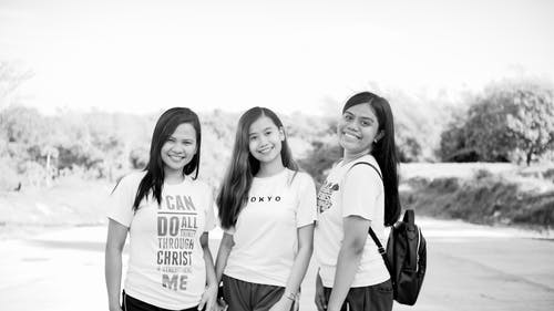 Black and white of positive young multiracial female friends in casual clothes looking at camera while standing on path near trees in daytime