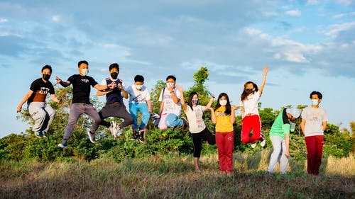 Group of happy teen jumping on green grass