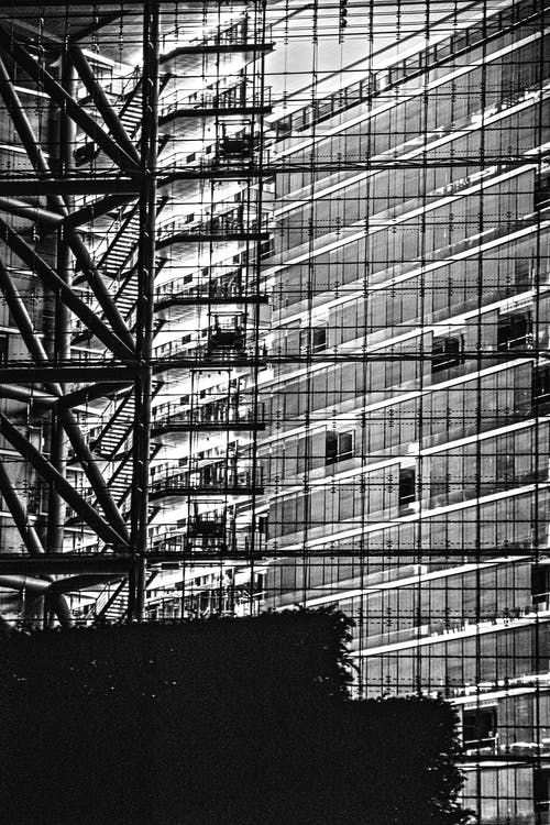 Grayscale Photo of Building With Glass Windows